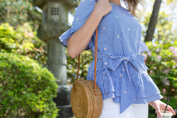 Fashion blogger Jessica Sturdy wearing a striped blue and white top with a bow tie and a circle rattan bag in Kyoto, Japan.