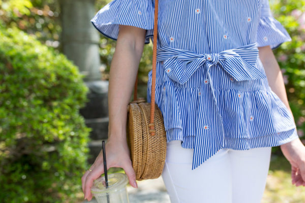Fashion blogger Jessica Sturdy wearing a striped blue and white top with a bow tie and a circle rattan wicker bag.