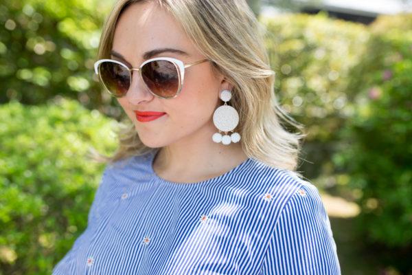 Fashion blogger Jessica Sturdy wearing white earrings, white sunglasses, and Rodin Lipstick in Tough Tomato.
