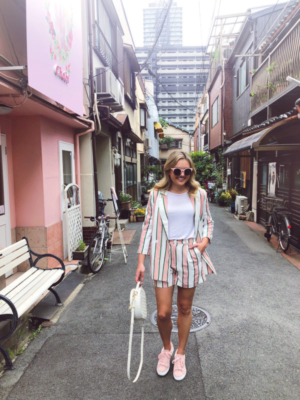 Jessica Sturdy wearing a white and pink striped blazer and short suit set, pink Vanessa Wu sneakers, pink sunglasses, and a round Brahmin white bag in the hipster neighborhood of Nakazakicho in Osaka, Japan.