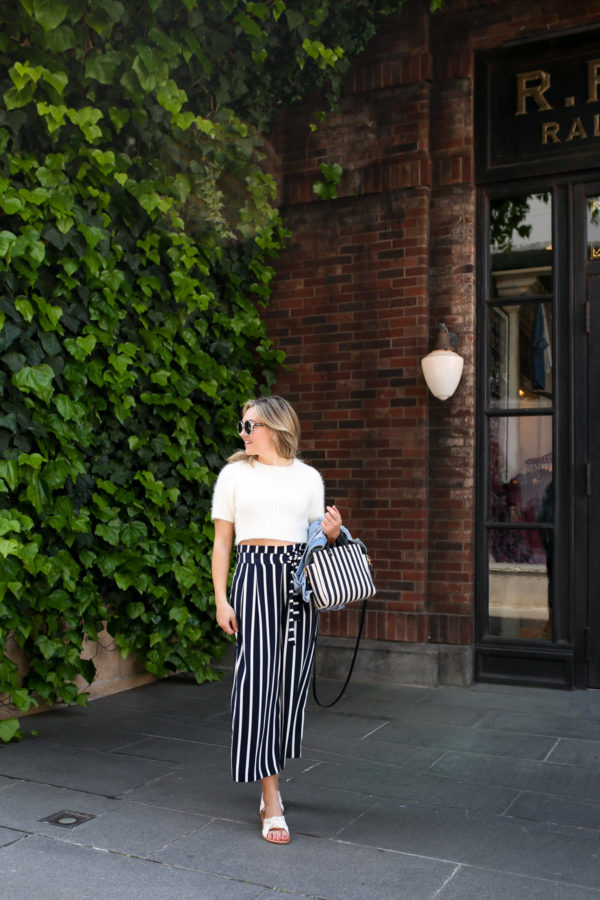 Travel blogger Jessica Sturdy wearing a crop top and high-waisted pants in front of Ralph Lauren in Tokyo.
