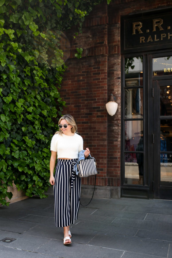 Blogger Jessica Sturdy wearing a cream short-sleeved sweater and striped wide leg pants in front of Ralph Lauren in Japan.