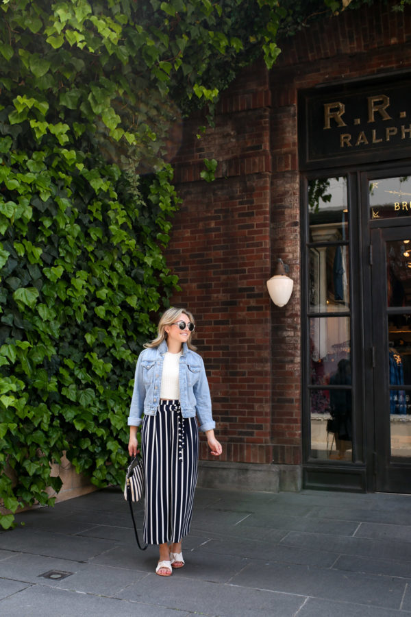 Blogger Jessica Sturdy wearing a denim jacket and striped wide leg pants in front of a green ivy and brick facade in Tokyo.