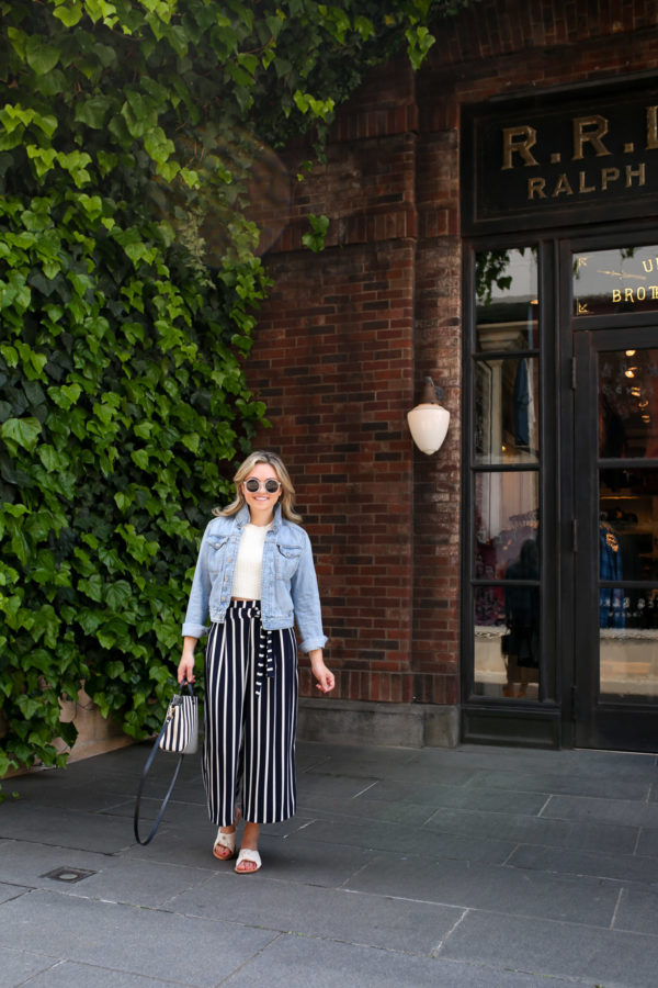 Fashion blogger Jessica Sturdy wearing a jean jacket, crop top, and striped wide leg pants in front of a green ivy and red brick wall in Tokyo, Japan.