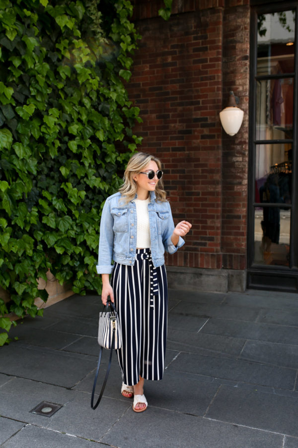 Jessica Sturdy wearing a cropped denim jacket with striped wide leg pants from Zara and a Clare V striped tote in Tokyo, Japan in front of the Ralph Lauren store.