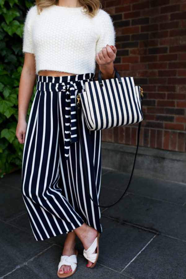 Fashion and travel blogger Jessica Sturdy wearing a crop top short-sleeved sweater with striped wide-leg pants and a Clare V mini stripe tote and slide sandals in Japan.