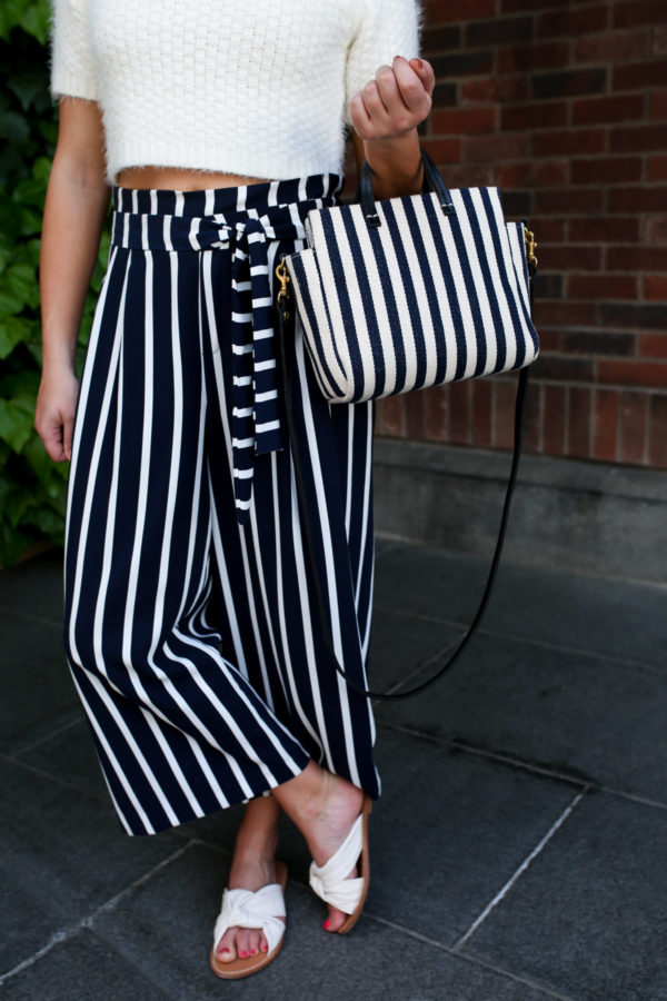Fashion blogger Jessica Sturdy styling a pair of Zara high-waisted striped wide-leg pants with a pair of Soludos knotted slide sandals in Tokyo, Japan.