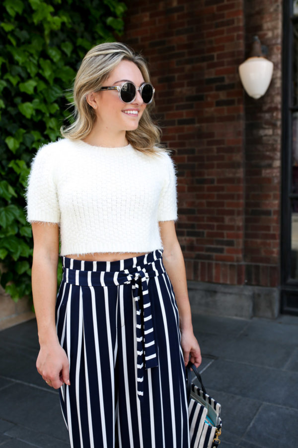 Jessica Sturdy wearing clear round Prive Revaux sunglasses in Tokyo Japan with a short-sleeve crop top sweater and high-waisted blue and white striped pants.