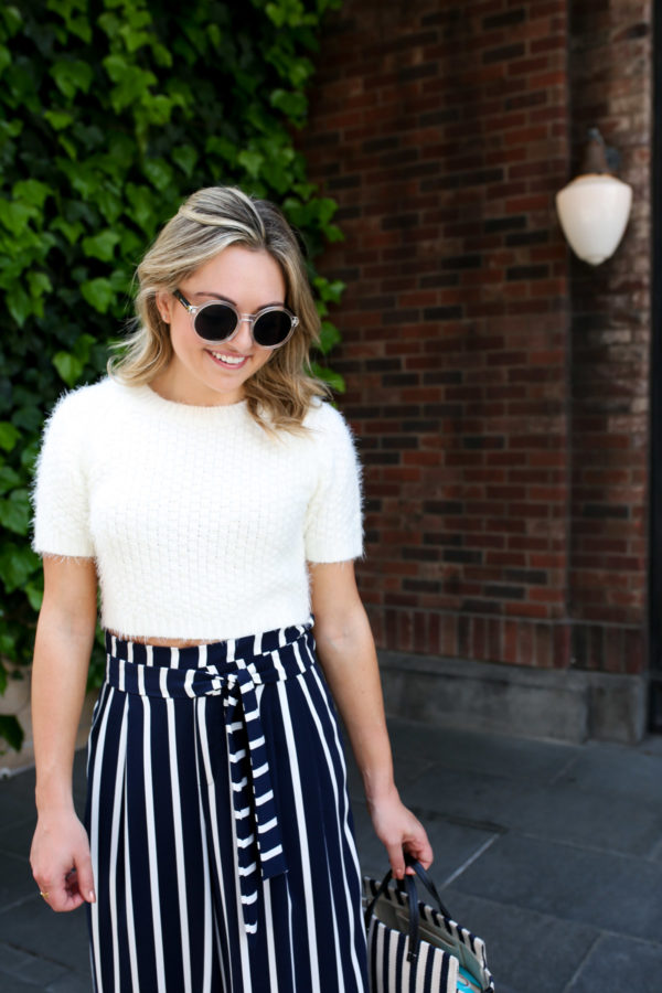 Jessica Sturdy wearing a pair of Prive Revaux clear round sunglasses with a short-sleeve cropped sweater and navy blue and white striped paper-bag pants in Tokyo.