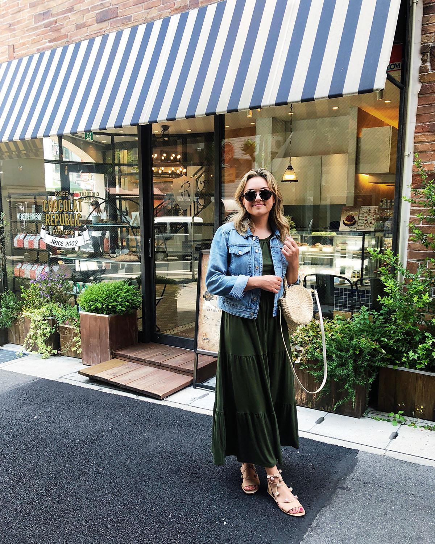 Jessica Sturdy in Kobe, Japan wearing an Old Navy maxi dress, denim jacket, Loeffler Randall pom pom sandals, Illesteva sunglasses, and a Clare V Straw tote
