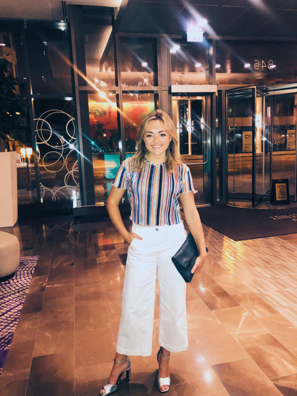 Jessica Sturdy wearing a Bershka striped top, Everlane white cropped wide leg jeans, Marc Fisher silver heels, and BaubleBar earrings.