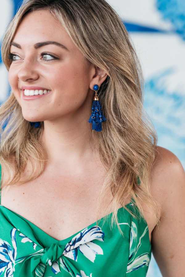 Jessica Sturdy wearing a pair of cobalt blue BaubleBar earrings with a green and blue floral dress.