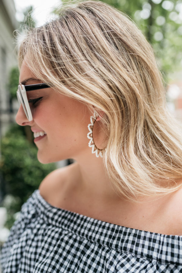 Jessica Sturdy wearing black and white sunglasses, Baublebar hoop earrings, and an off the shoulder gingham dress.