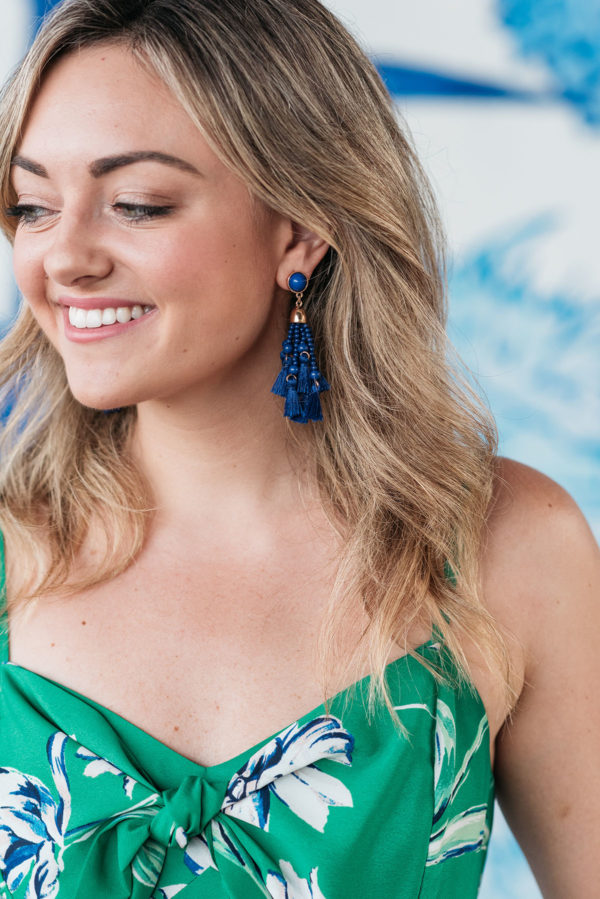 Jessica Sturdy wearing a pair of BaubleBar tassel earrings with a green floral dress.