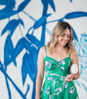 Chicago lifestyle and fashion influencer Jessica Sturdy wearing a green floral dress in front of a blue and white street art mural at Ping Tom Park.