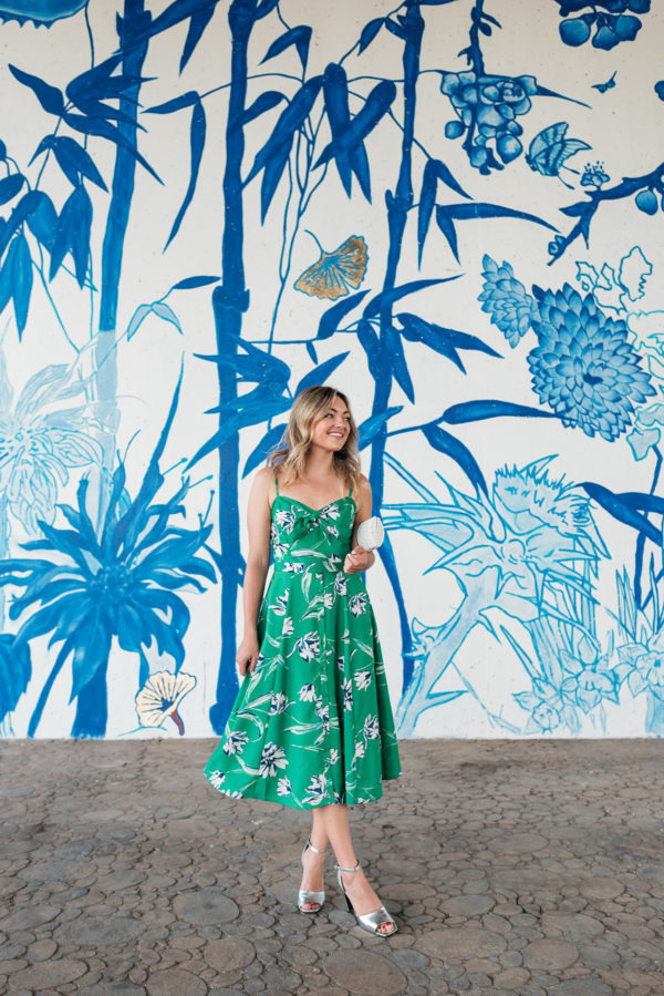 Chicago personal stylist Jessica Sturdy wearing a green floral midi dress in front of a blue and white chinoiserie mural in Chinatown in Chicago.