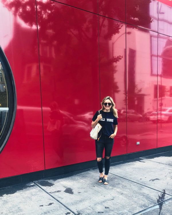 "Jessica Sturdy wearing a Cynthia Rowley ""Cali York"" tee with black ripped jeans in Chicago in front of Ikram."
