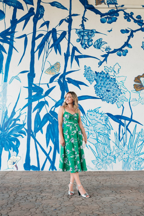 Chicago travel blogger Jessica Sturdy wearing a green floral dress in front of the Asian-inspired blue and white chinoiserie mural at Tom Ping Park in Chinatown, Chicago.