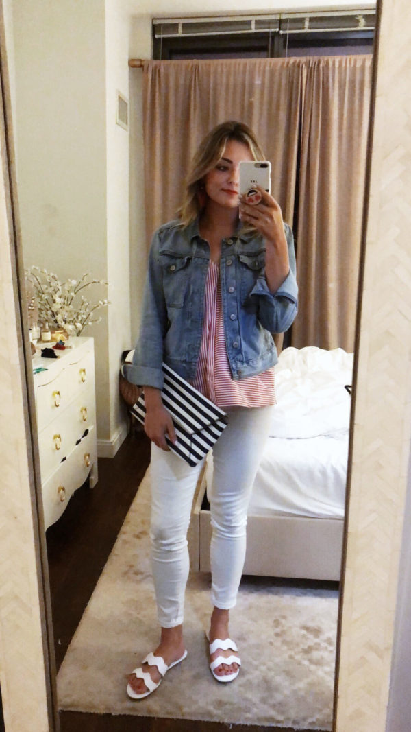 Jessica Sturdy wearing white jeans, a red and white striped top, a denim jacket, white sandals, and a navy blue striped clutch.
