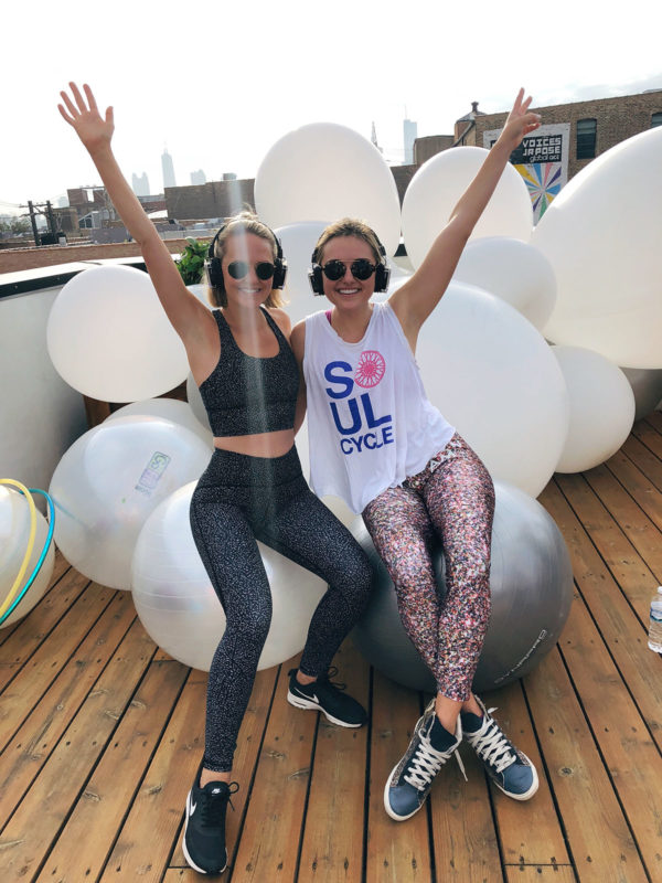 Kelly Chrischilles and Jessica Sturdy at Daybreaker Chicago in the summer on a rooftop in the West Loop with city skyline views