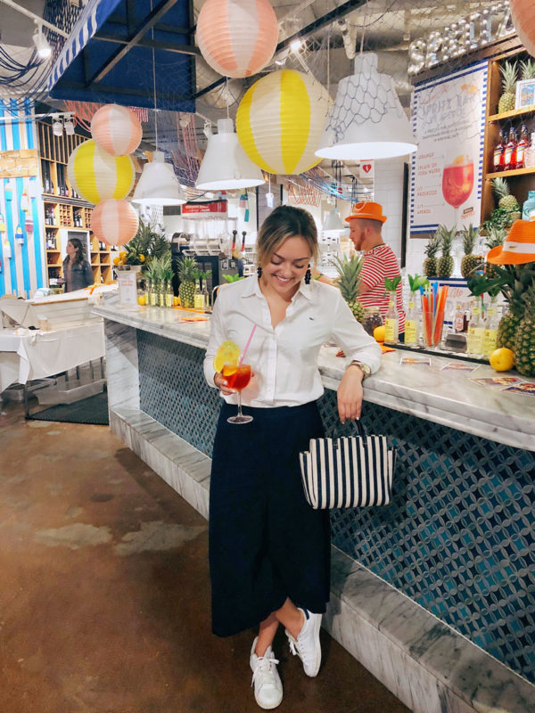 Jessica Sturdy at the Eataly Chicago Sabbia opening with an Aperol Spritz wearing a white button front shit, wide leg pants, Adidas stan smith sneakers, and a stripe Clare V bag.