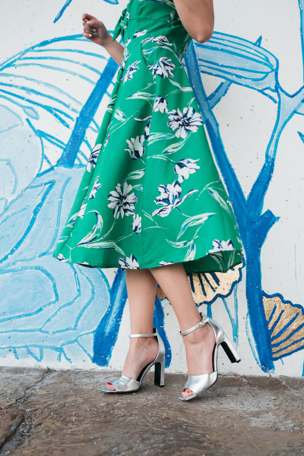 Jessica Sturdy wearing a green, white, and blue floral printed midi dress with Marc Fisher silver ankle-strap pumps.