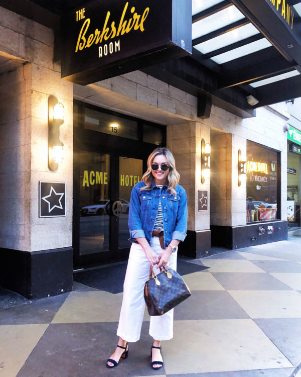 Chicago lifestyle blogger wearing a denim jacket, striped shirt, wide leg white jeans, and a Louis Vuitton Speedy bag.