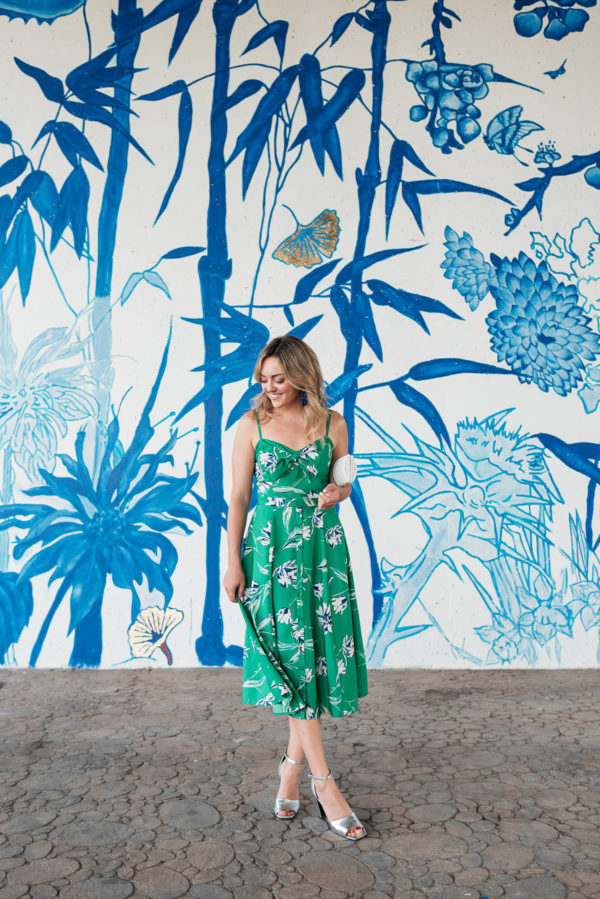 Chicago blogger Jessica Sturdy styling a green floral dress from Nordstrom with silver pumps and a white wicker clutch.