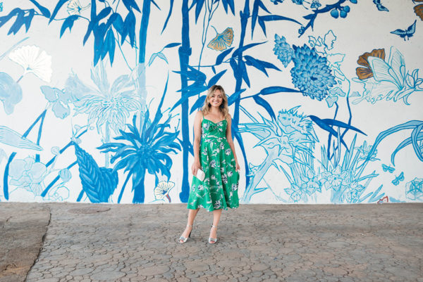 Popular Chicago blogger Jessica Sturdy taking photos in front of a blue and white mural in Chinatown.