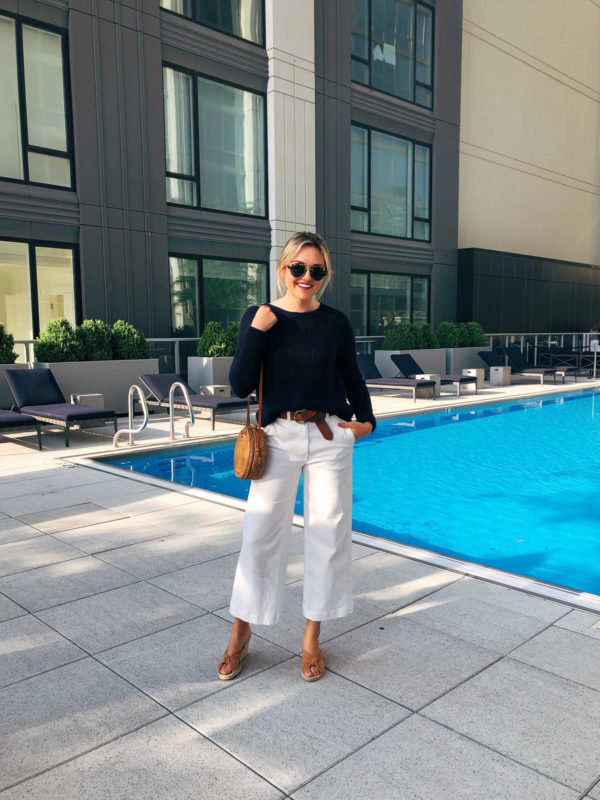 Chicago lifestyle blogger Jessica Sturdy wearing a navy blue sweater, brown leather belt, white cropped wide leg jeans, Illesteva sunglasses, wedge espadrille sandals, and a round rattan bag at Two West Delaware luxury apartment building.