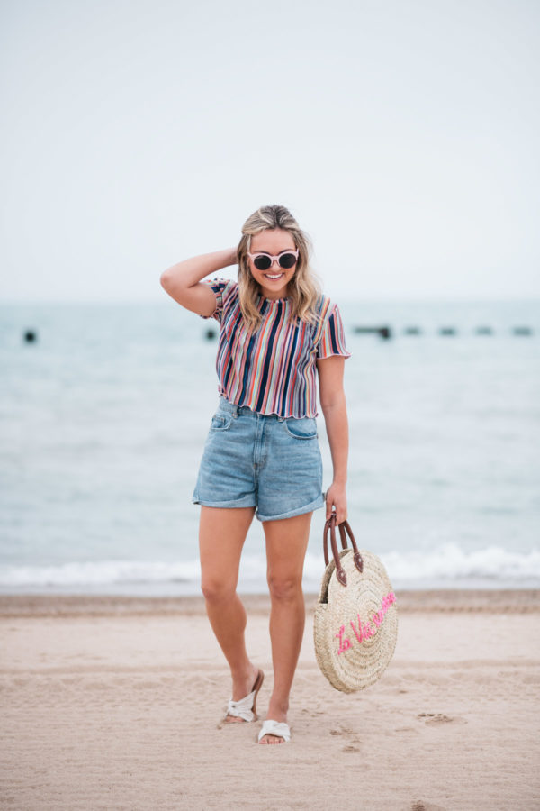 Fashion blogger Jessica Sturdy wearing pink sunglasses, a Bershka candy striped ruffled hem short sleeve cropped top, Cotton On high-rise shorts, and Soludos knotted slides with a White Elephant Designs embroidered tote by Lake Michigan in Chicago.