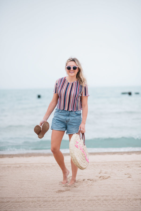 Jessica Sturdy with a La Vie en Rose embroidered straw tote, created in collaboration with White Elephant Designs, and wearing pink sunglasses, a Bershka striped cropped top and Cotton On high-rise flashback shorts with Soludos slide sandals at the North Avenue Beach in Chicago.