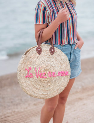 """Jessica Sturdy wearing a Bershka striped ruffled hem cropped top with Cotton On high-rise flashback shorts with a """"La Vie en Rose"""" embroidered straw tote created in collaboration with Jessica Sturdy."""