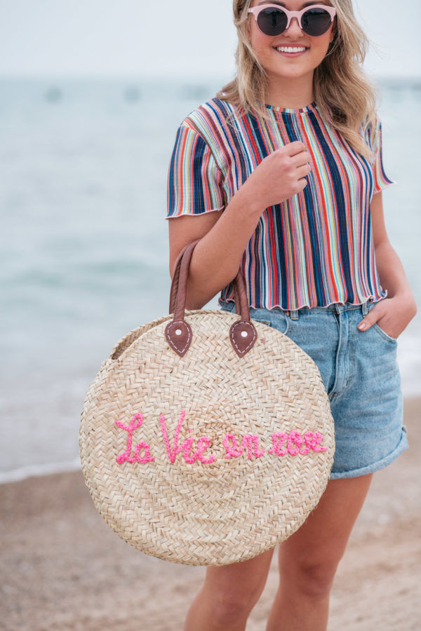 "Jessica Sturdy wearing a Bershka striped ruffled hem cropped top with Cotton On high-rise flashback shorts with a ""La Vie en Rose"" embroidered straw tote created in collaboration with Jessica Sturdy."