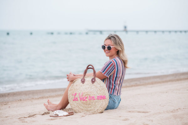 "Chicago fashion blogger Jessica Sturdy wearing pink sunglasses, Bershka candy striped shirt, Cotton On high-rise shorts with Soludos slide sandals and a White Elephant Designs embroidered straw tote with ""La Vie en Rose"" collaboration with Jessica Sturdy at Lake Michigan in Chicago."