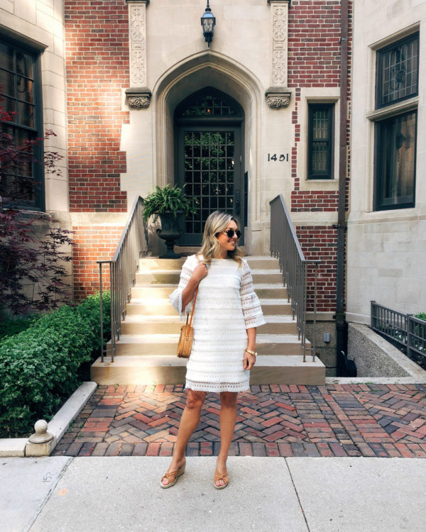 Chicago personal stylist Jessica Sturdy wearing a white lace dress by Sail to Sable, a round rattan bag, and Soludos wedge espadrilles.