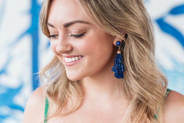 Bows & Sequins wearing a set of blue tassel earrings.