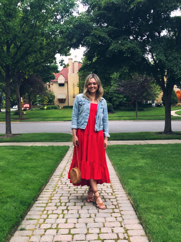 Jessica Sturdy wearing a red tiered maxi dress with a denim jacket, lace-up sandals, and a round wicker bag.
