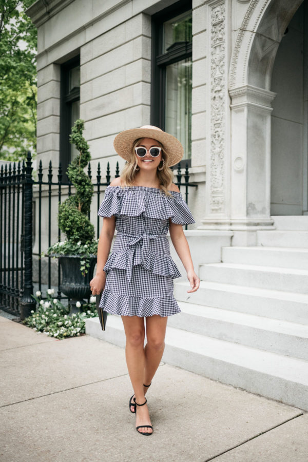 Jessica Sturdy wearing a ruffled off the shoulder gingham dress from White Elephant Designs with white and black sunglasses, black block heels, and a straw hat.