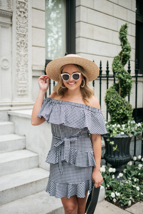Fashion blogger Jessica Sturdy wearing a straw hat, black and white sunglasses, and an off the shoulder gingham dress with an Old Navy black clutch.
