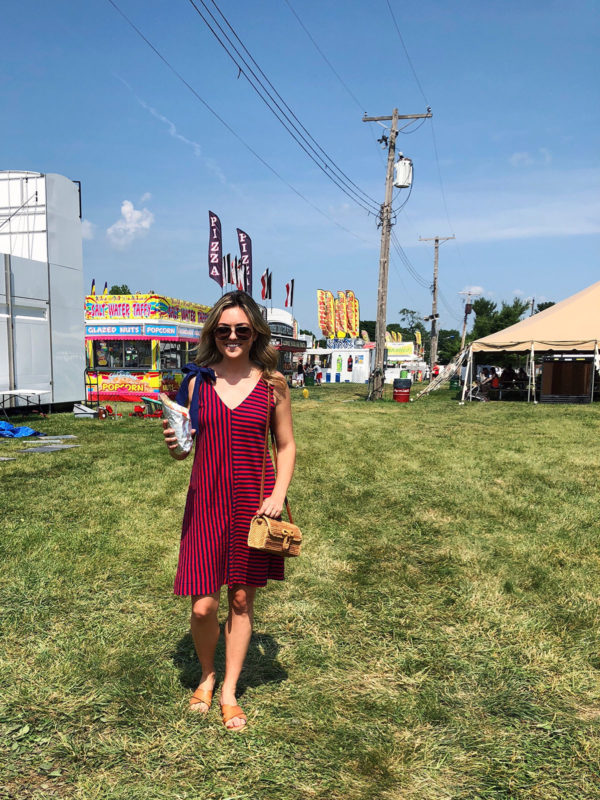 Jessica Sturdy wearing a red and blue striped Vineyard Vines dress with a bow tie shoulder and a wicker bag at the Sangamon County Fair in Illinois.