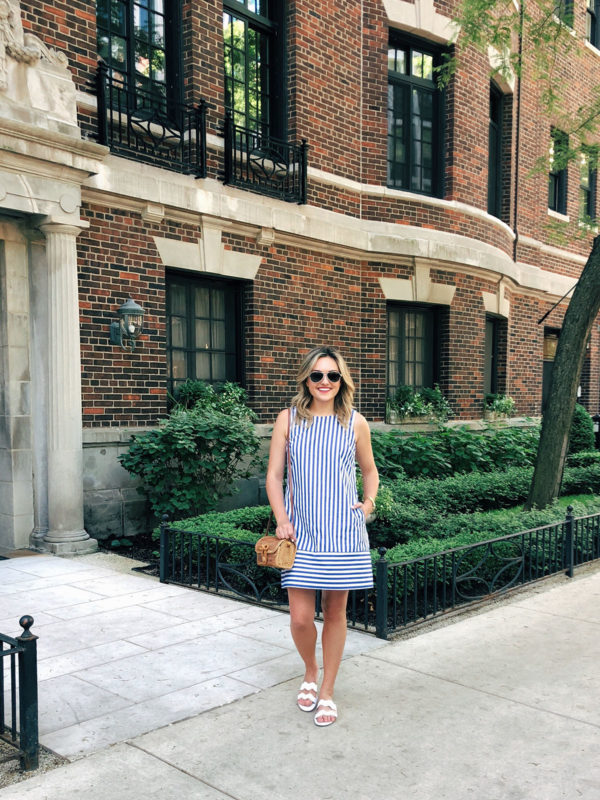 Jessica Sturdy styling a blue and white striped Vineyard Vines dress with white scalloped sandals and a wicker crossbody bag.