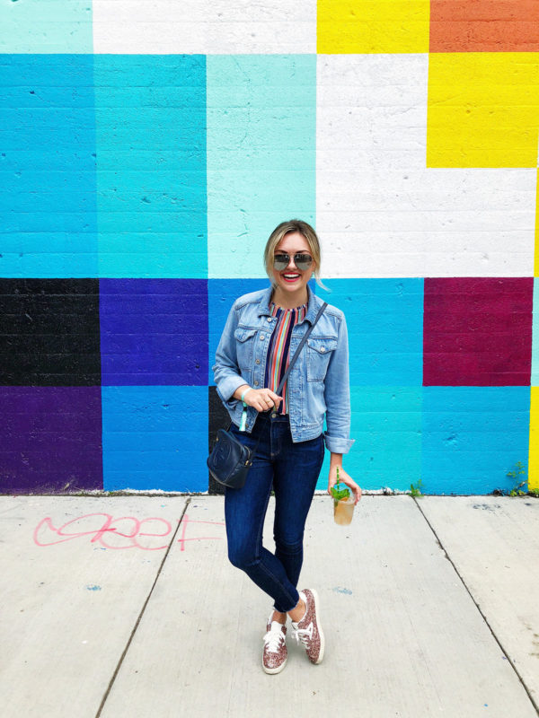 Chicago lifestyle blogger Jessica Sturdy wearing a denim jacket with blue jeans, glitter sneakers, Celine sunglasses, and a Gucci crossbody bag at a concert in Chicago in front of a colorful mural wall.