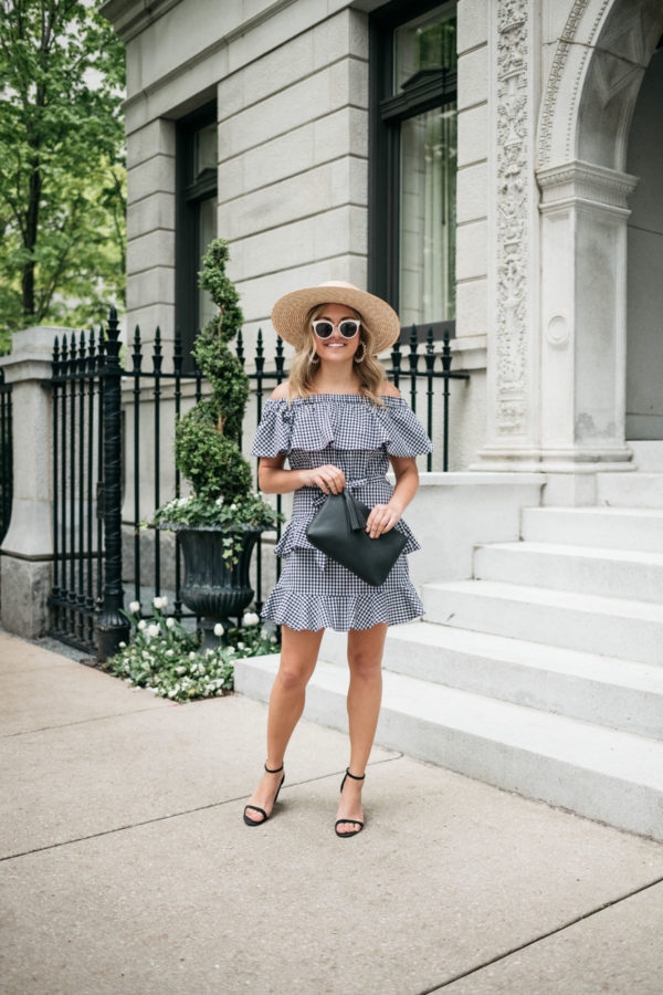 Fashion blogger Jessica Sturdy wearing a straw hat, black and white sunglasses, black block heels, and an off the shoulder gingham dress with an Old Navy black clutch.