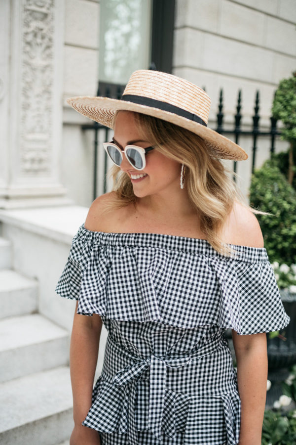 Jessica Sturdy from Bows & Sequins wearing Baublebar hoop earrings, a monogrammed straw hat, and a White Elephant Designs off the shoulder ruffled gingham dress.