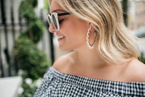 Jessica Sturdy wearing Baublebar white hoop earrings, black and white sunglasses, and an off the shoulder gingham dress from White Elephant Designs.