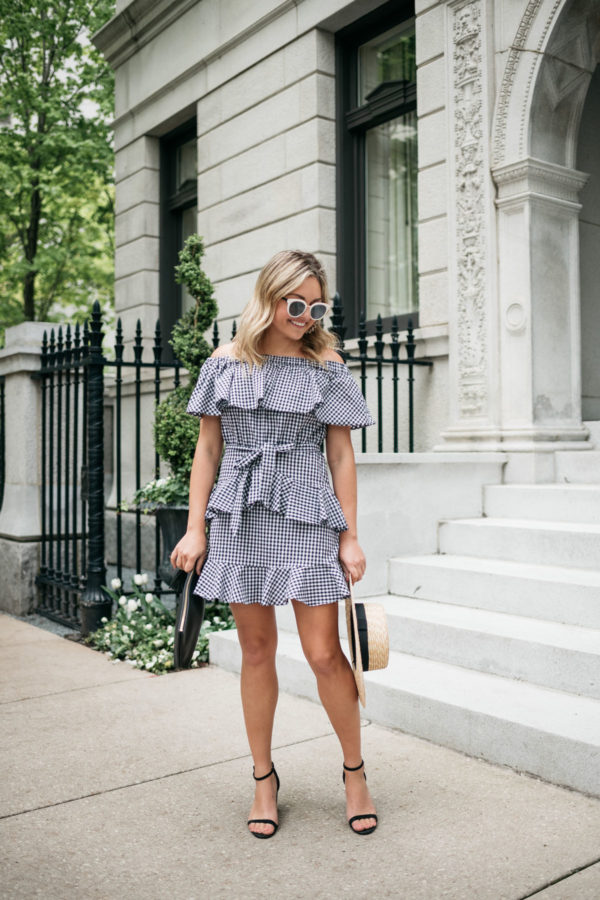 Chicago fashion blogger Jessica Sturdy wearing a ruffled tie-waist off the shoulder gingham dress with black block heels, a monogrammed straw hat, and black and white sunglasses.