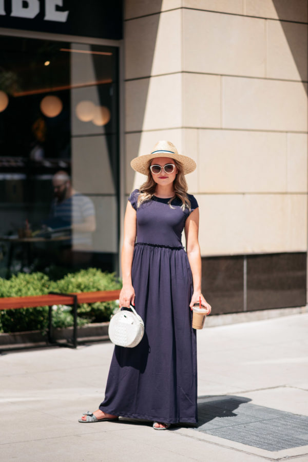 Chicago fashion blogger Jessica Sturdy wearing a navy blue maxi dress and straw hat.