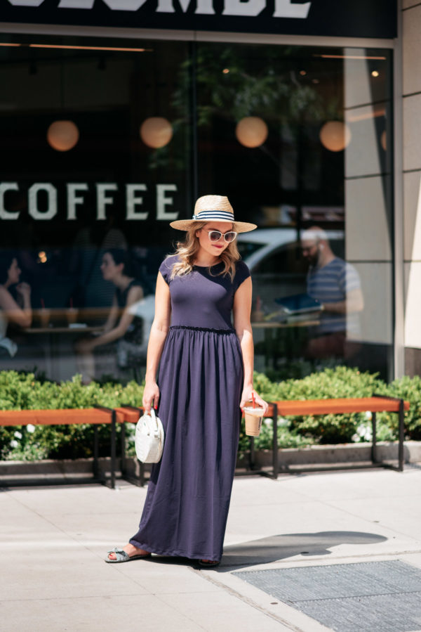 Chicago beauty blogger Jessica Sturdy wearing a blue maxi dress and striped straw hat in front of La Colombe Coffee in the Gold Coast.