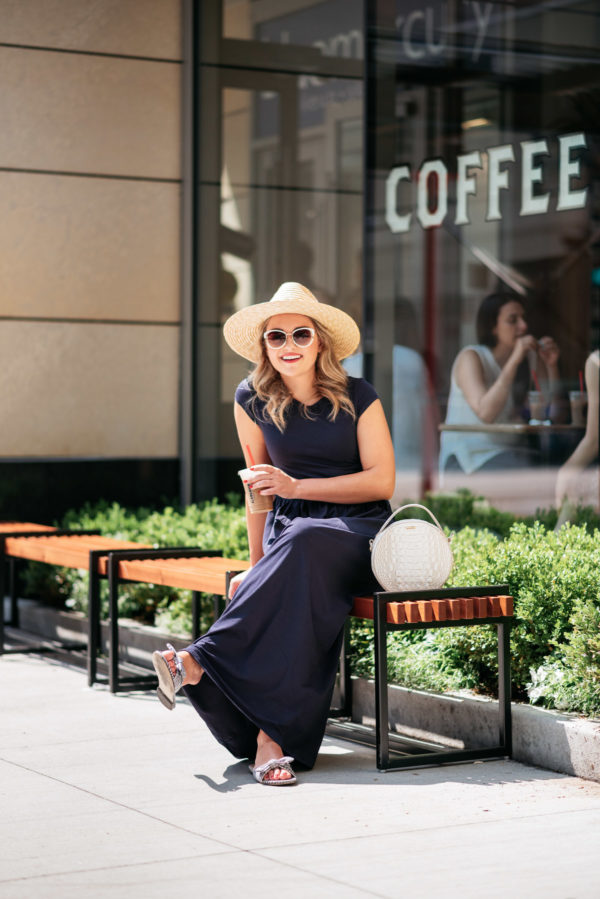 Chicago lifestyle blogger Jessica Sturdy wearing a straw hat, white circle handbag, and blue maxi dress getting coffee in the Gold Coast in Chicago.